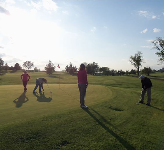 a photo of four people at on the putting green at Sugar Creek Golf Course